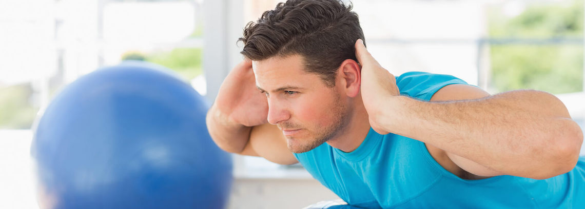 image of man doing back stretch with medicine ball